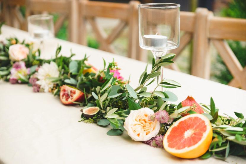 girlanda z owocami granatu i grejpfruta jako dekoracja stołu