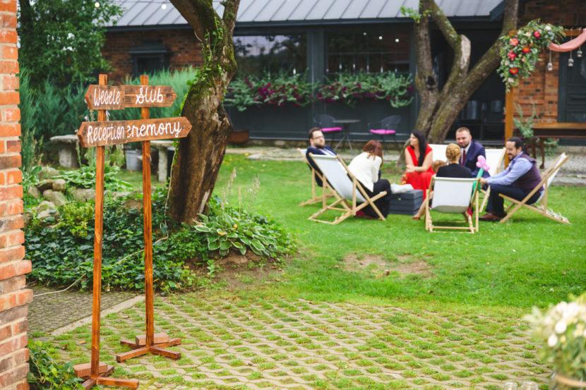 drogowskazy ślubne i leżaki jako dekoracja ślubu w plenerze