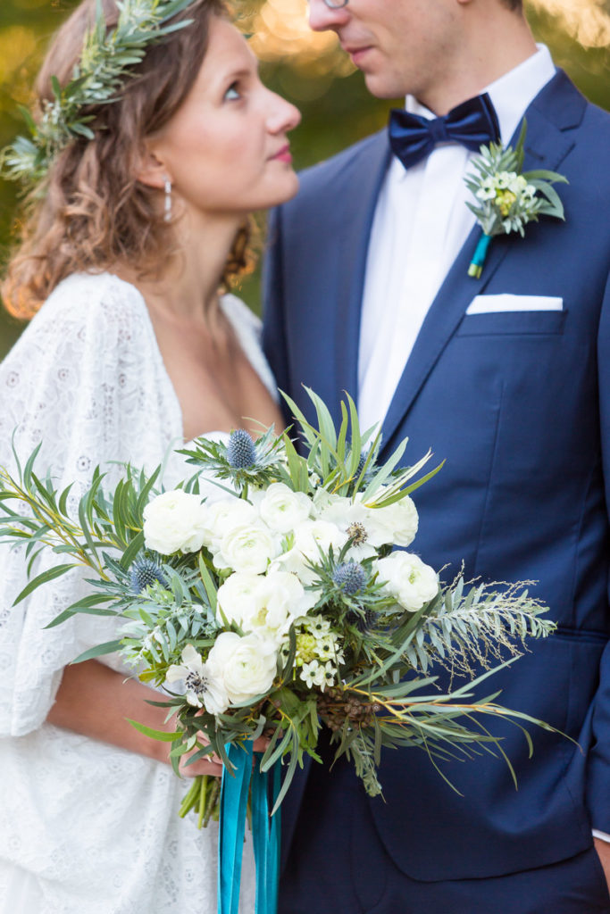 bukiet z białych kwiatów w stylu botanicznym oraz wianek z zielonych listków