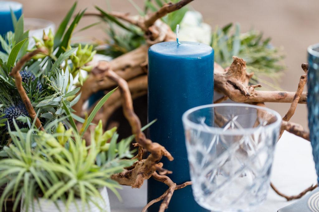 świece w kolorze granatowym i konary jako elementy aranżacji stołu
