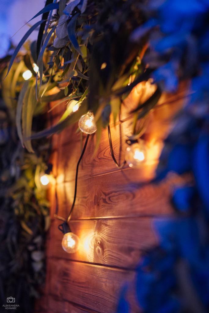żarówki, zieleń i drewno jako dekoracja tła za parą młodą