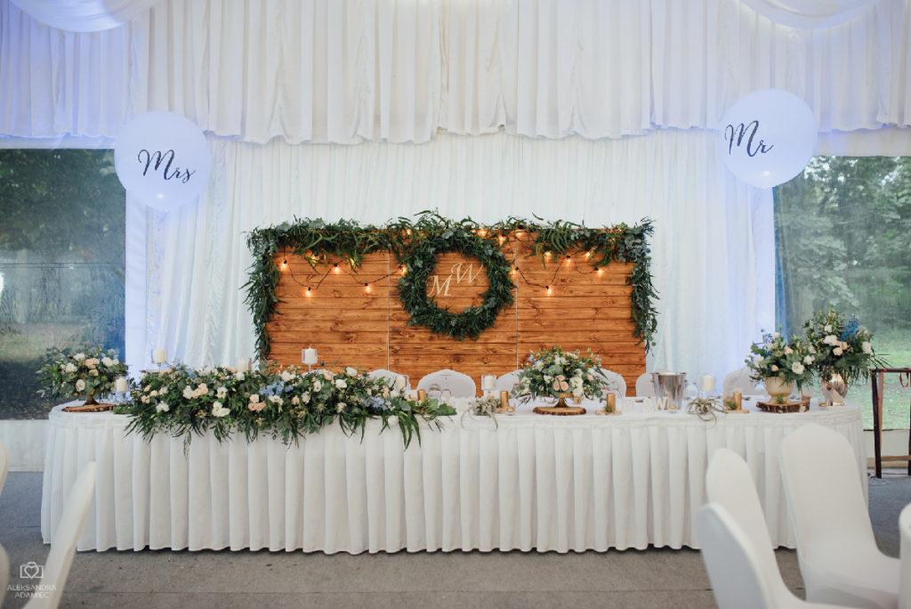 aranżacja stołu prezydialnego składająca się z kompozycji w wazach i paterach i podłużnej girlandy