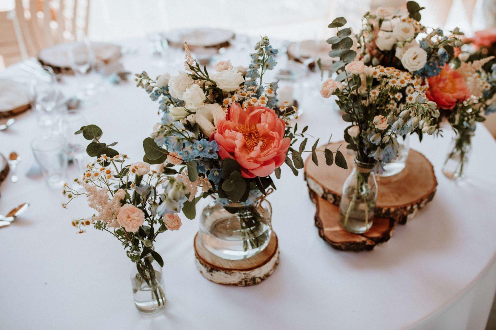 kwiaty w kolorach koralowych i błękitnych w słojach i butelkach na drewnie jako dekoracja stołu państwa młodychm
