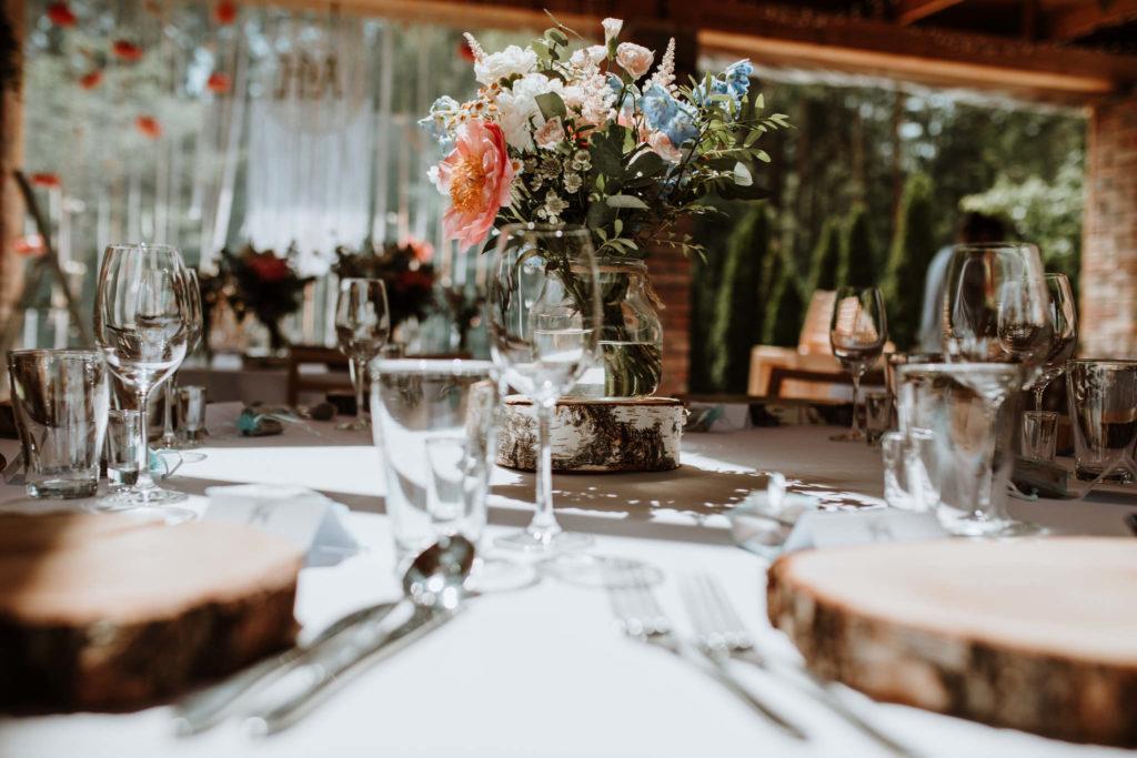 bukiet z penii ostróżki goździka w słoju jako aranżacja stołu na wesele