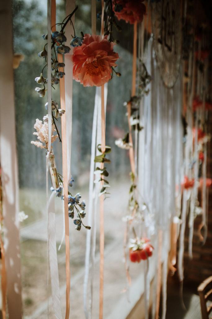 kwiaty zawieszane na wstążkach jako tło za parą młodą w stylu boho