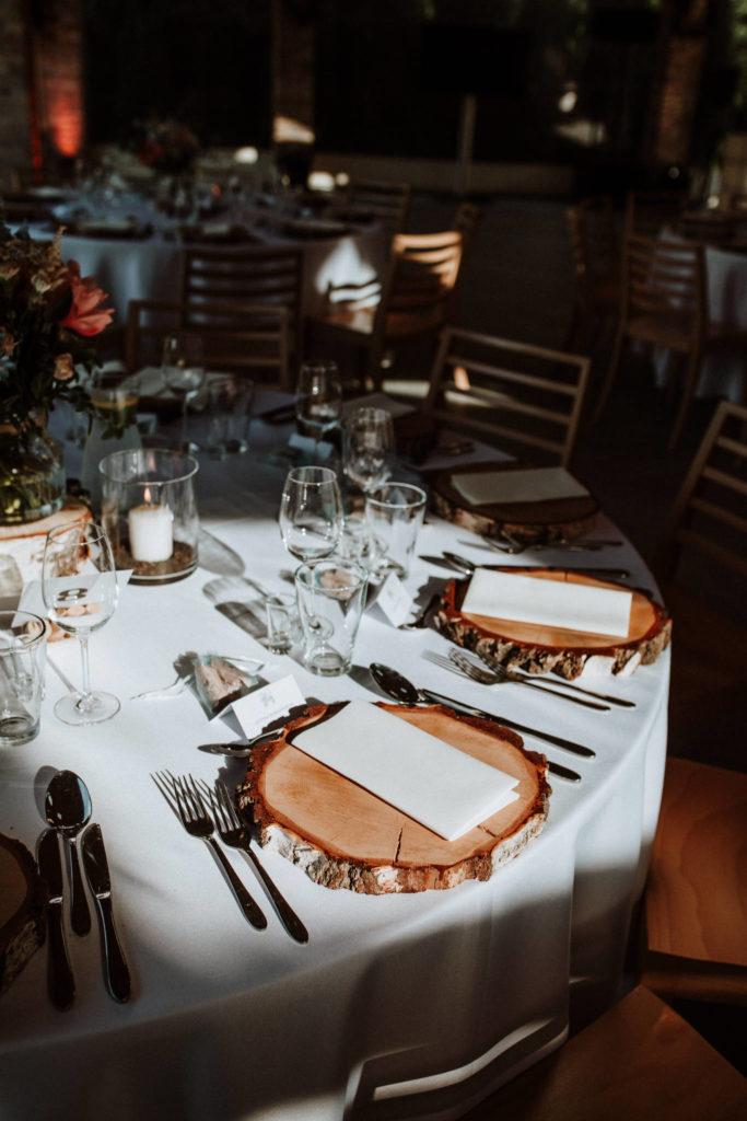 drewniane dodatki w postaci plastrów drzewa jako dekoracja stołów gości