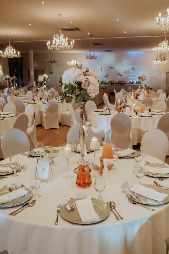 wysoka kompozycja kwiatowa na srebrnym stojaku w stylu glamour w pastelowych barwach