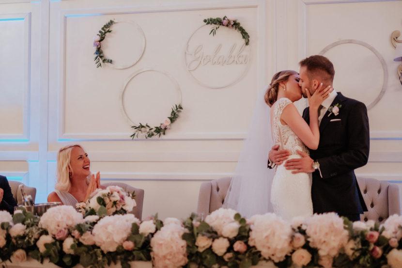 aranżacja stołu pary młodej w postaci długiej girlandy z kwiatów i kół srebrnych zielenią i kwiatami
