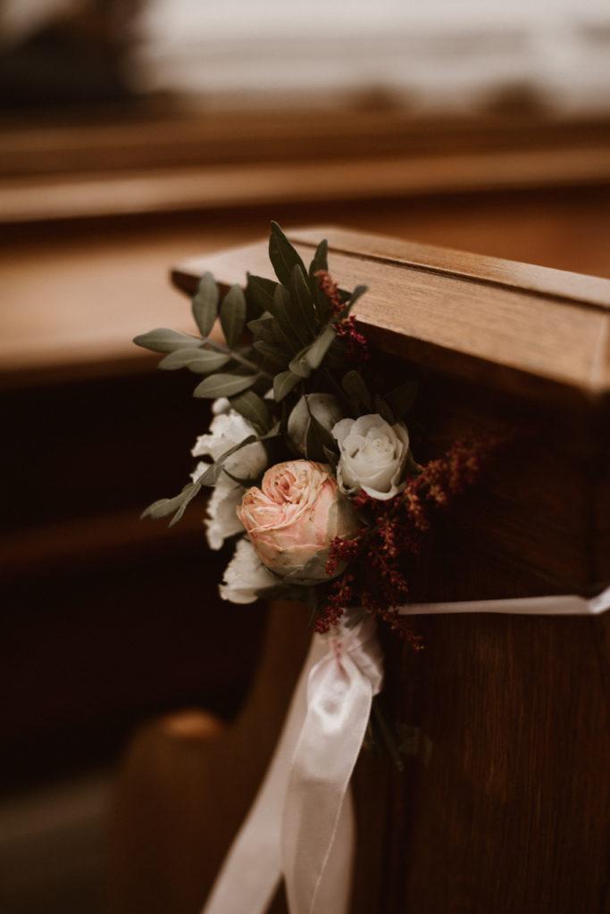 bukiecik z pastelowych kwiatów z dodatkiem bordo i wstążką jako dekoracja ławki do ślubu