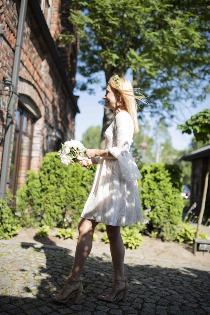 panna młoda w wianku z zielonych listków oliwki i z białym bukiecikiem peonii