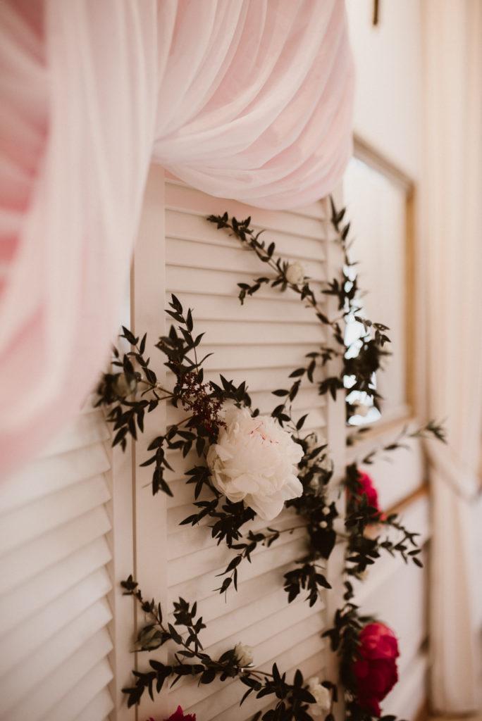 dekoracja kwiatowa na parawanie białym jako aranżacja tła z parą młodą