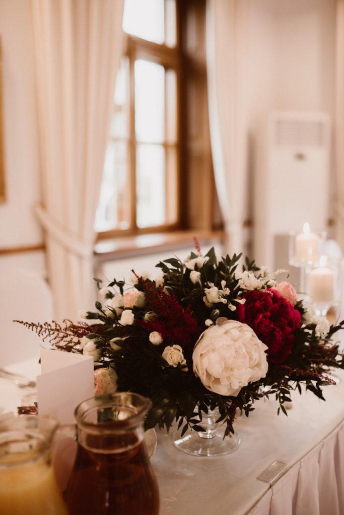 kompozycja w szklanym naczyniu z peoniami i dodatkami kwiatowymi w stylu glamour