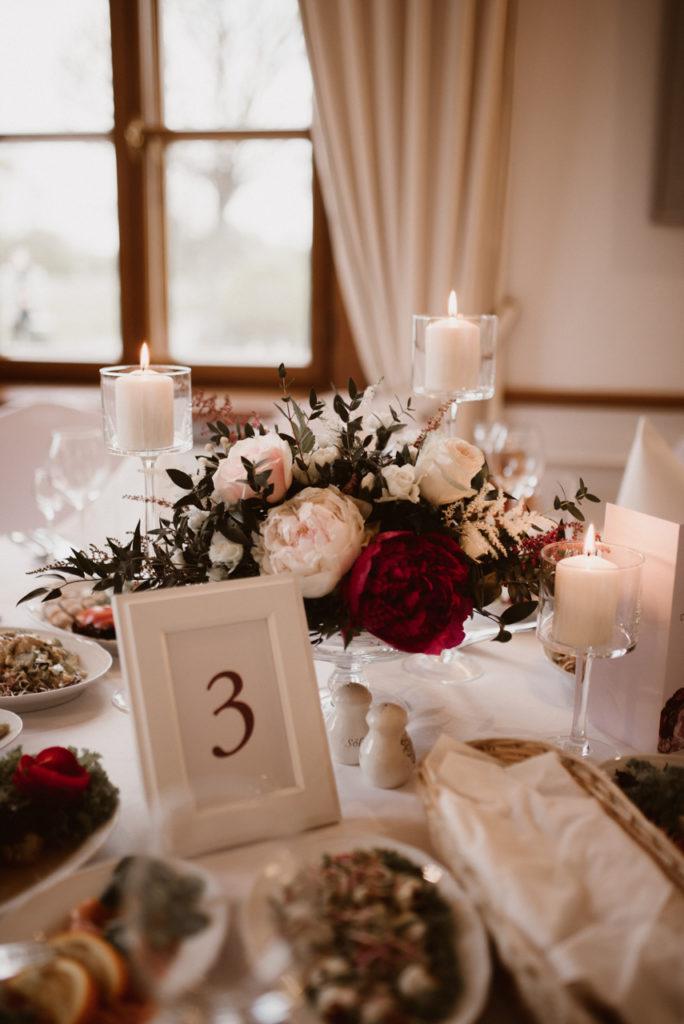 kwiaty w szklanej paterze ze świecami w szkle i białą ramką na numer stołu jako dekoracja wesela