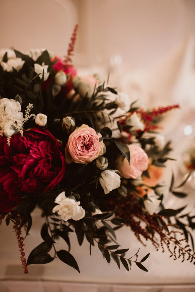 kwiaty w kolorze białym różowym i czerwonego wina z dodatkiem eukaliptusa i ruskusa jako kwiaty na stoły weselne