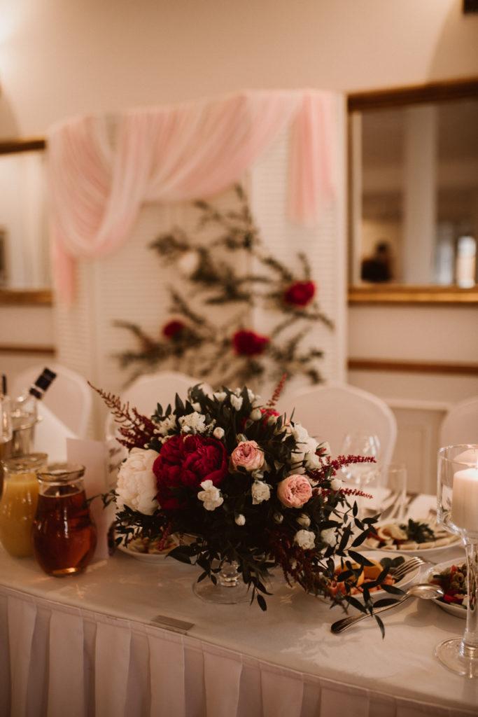 aranżacja stołu pary młodej ze świec i kompozycji kwiatowych w niskich szklanych naczyniach na nóżce