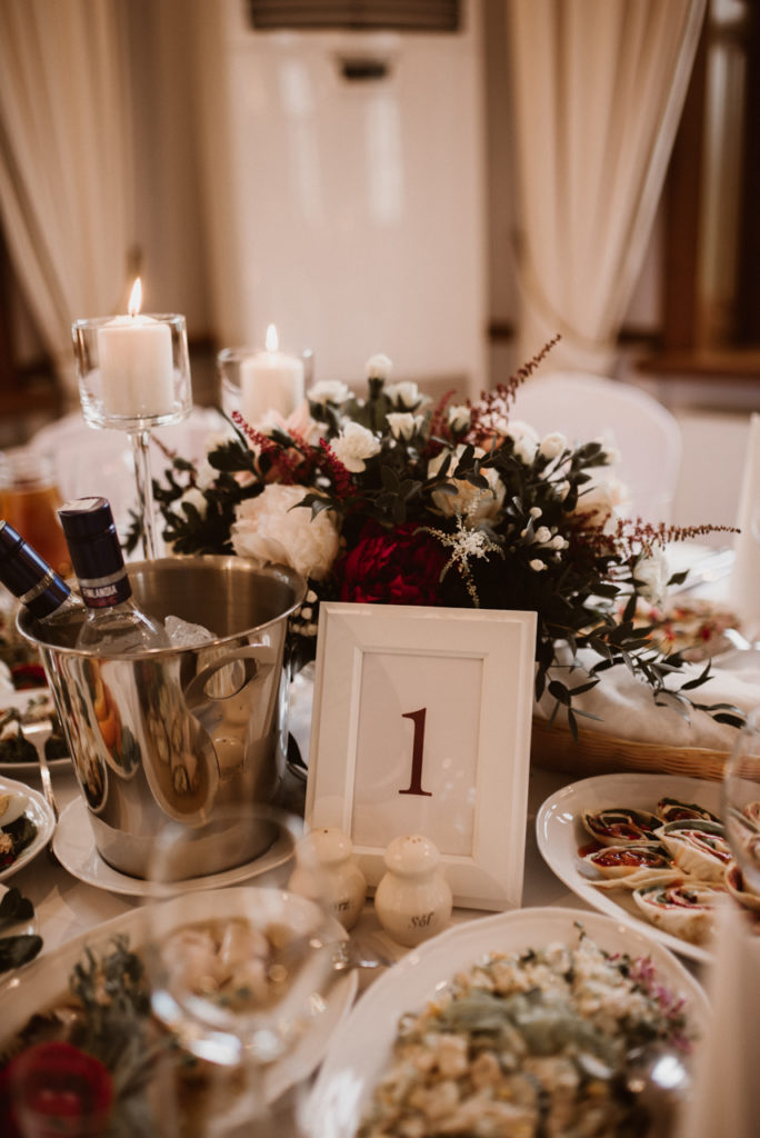 niska dekoracja kwiatowa na stoły gości z ramką białą na numerek i świecami w szklanych kielichach