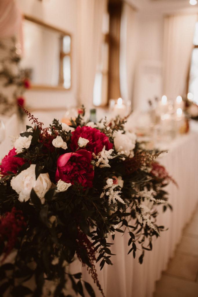 kompozycja kwiatowa leżąca na stole prezydialnym jako asymetryczna aranżacja ze świecami