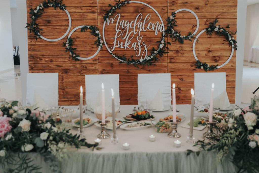 aranżacja stołu pary młodej z długich świec szarych i różowych i rustykalną ścianką ze desek