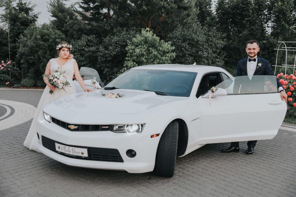 para młoda pozująca przy białych samochodzie udekorowanym kwiatami do ślubu