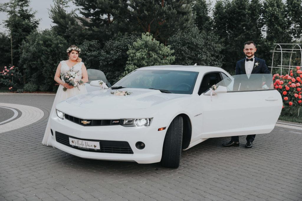 szczęśliwa para młoda pozująca z kwiatami przy ozdobionymi samochodzie