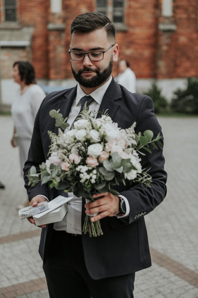 świadek trzymający duży bukiet panny młodej do ślubu