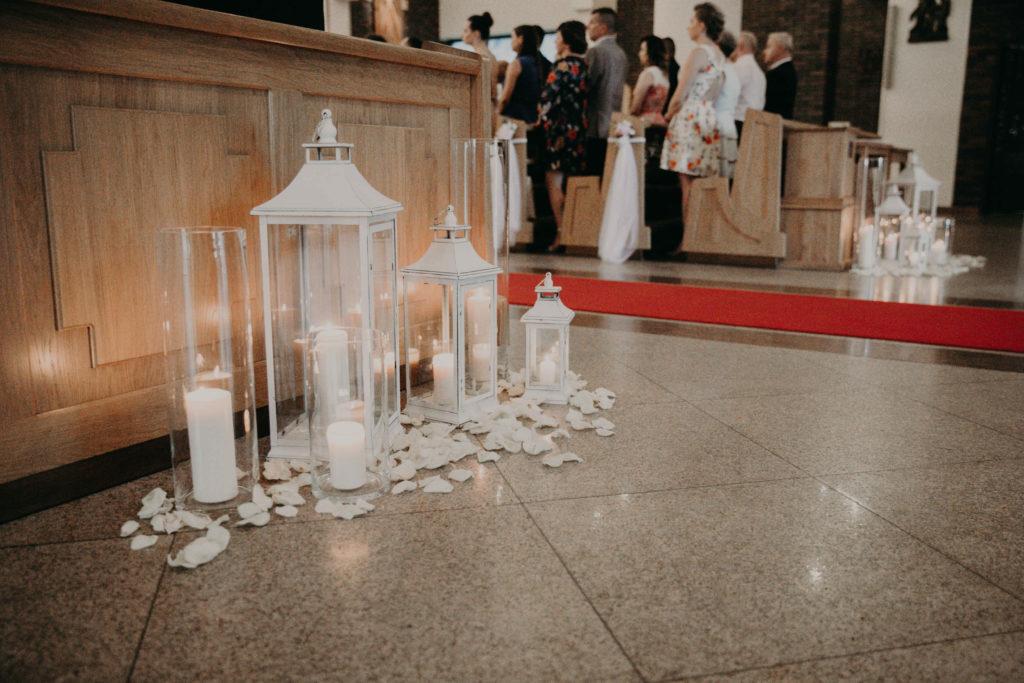 lampiony białe ze świecami tuby szklane i płatki róż rozsypane pomiędzy jako dekoracja nawy głównej kościoła