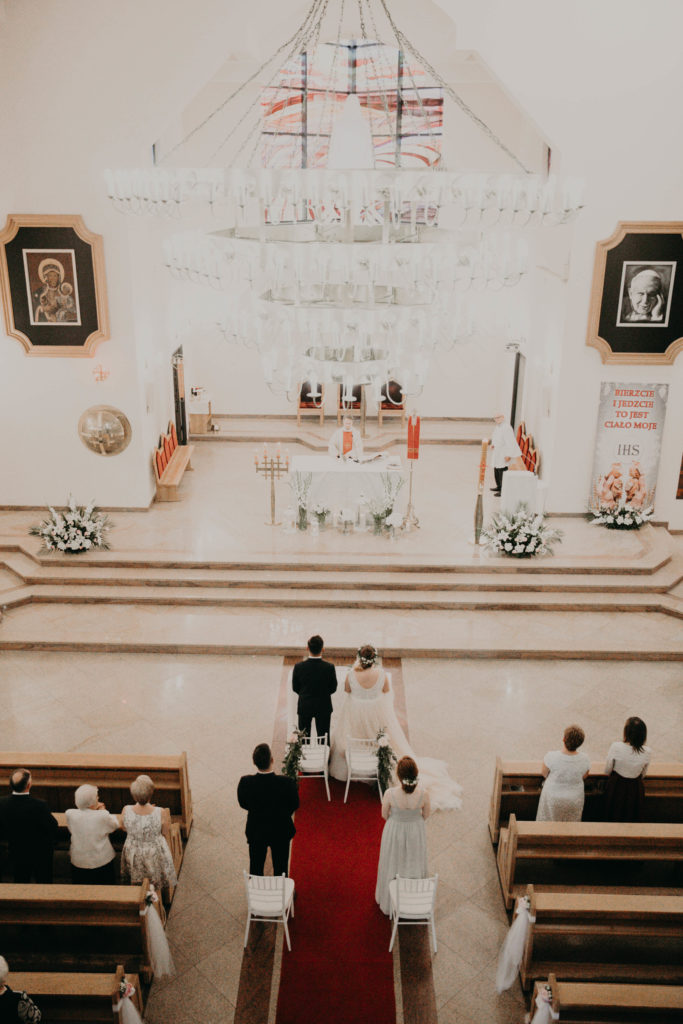 wystrój kościoła do ślubu białymi kwiatami i białymi krzesłami