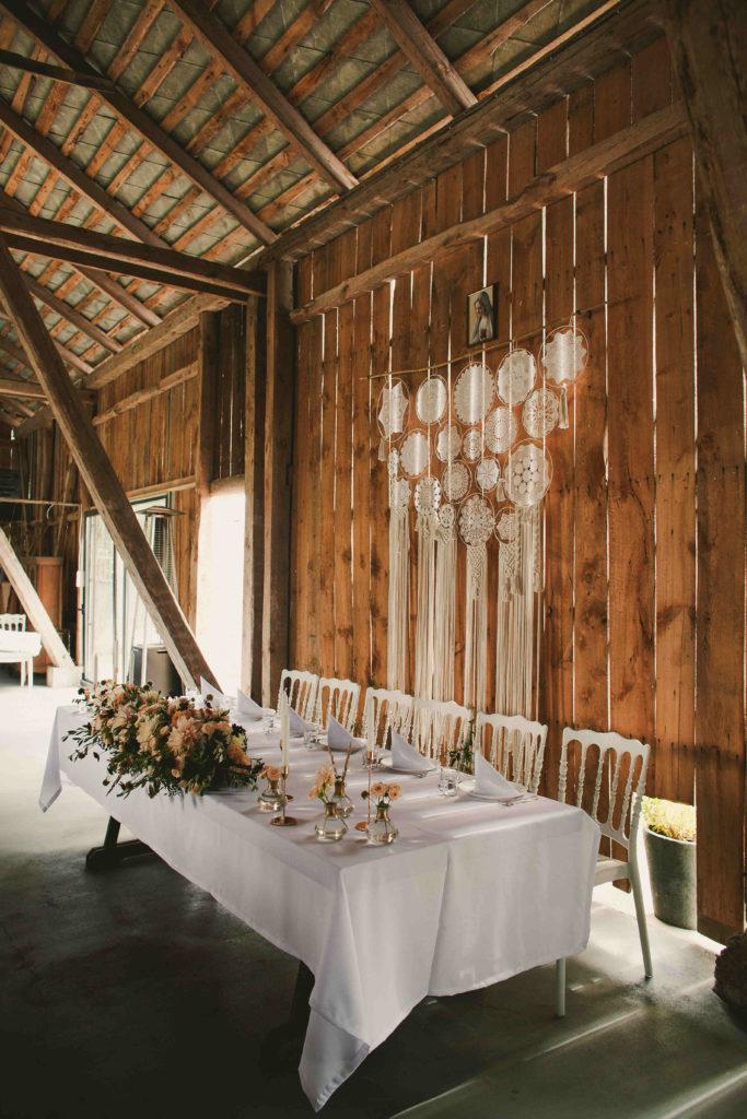 dekoracja stołu pary młodej rustykalnymi kwiatami ze złotymi akcentami na weselu w stodole