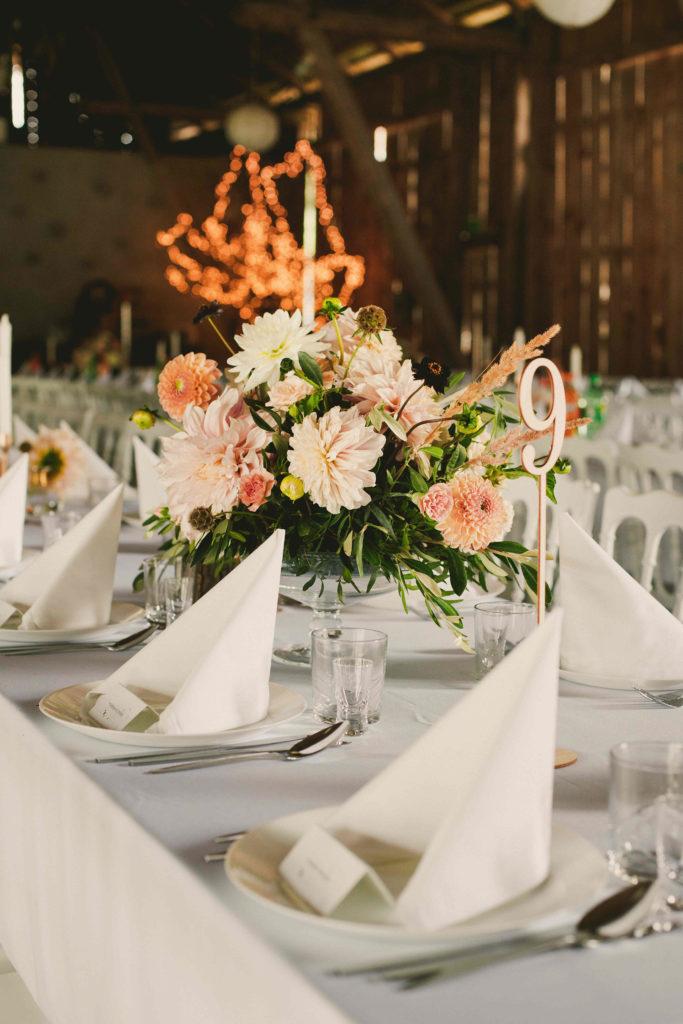 aranżacja z kwiatów w kolorach brzoskwiniowo beżowych jako dekoracja stołu gości w stodole weselnej