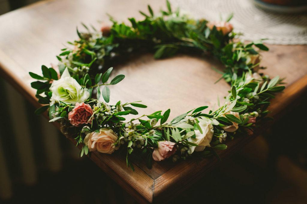 wianek z zielonych listków i kwiatów w kolorach pastelowo brzoskwiniowych