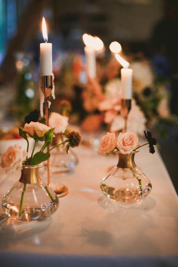 buteleczki z pojedynczymi kwiatami oraz długie świece w złotych świecznikach jako aranżacja stołów gości w stodole