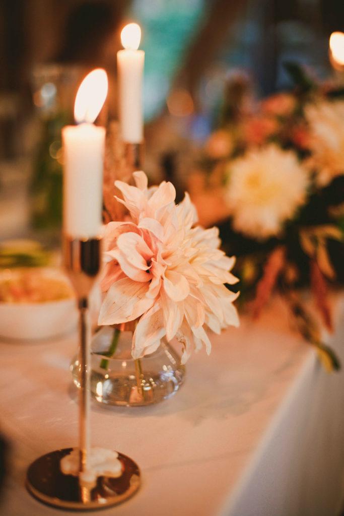 złoty świecznik na długą świecę i kwiaty w małych butelkach jako dekoracja stołów w stylu boho glam