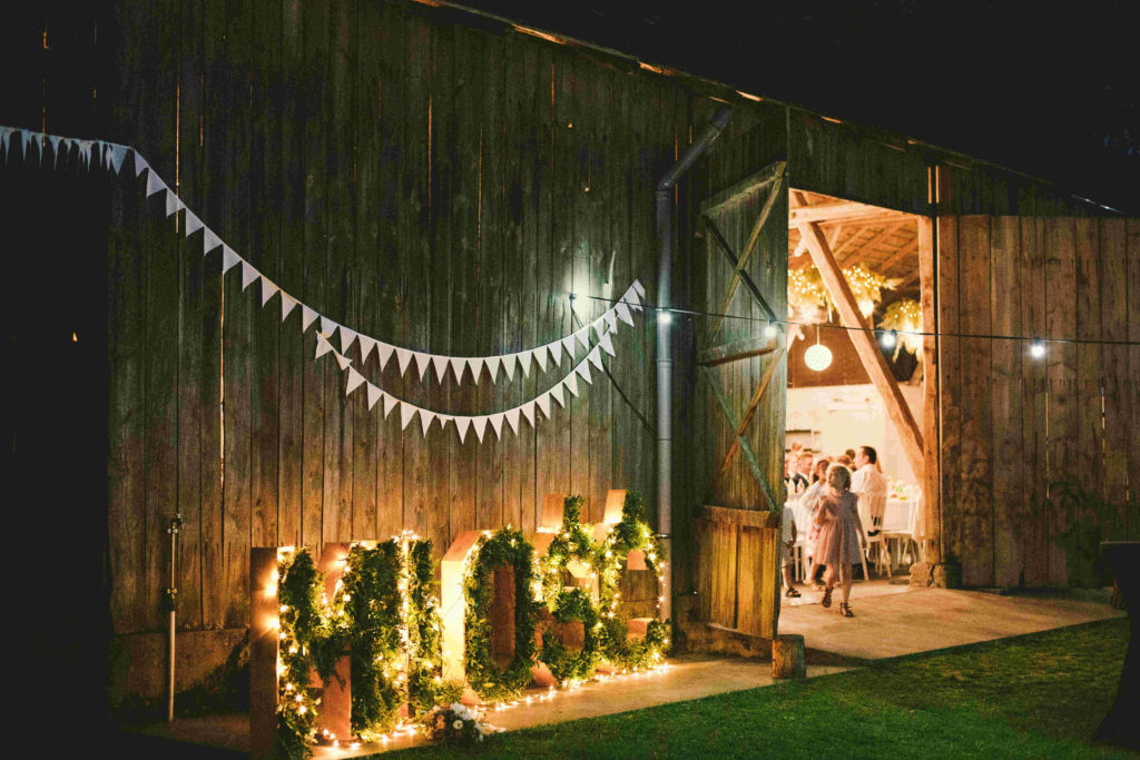 drewniany napis miłość wypełniony zielonymi gałązkami jako dekoracja wesela w stodole