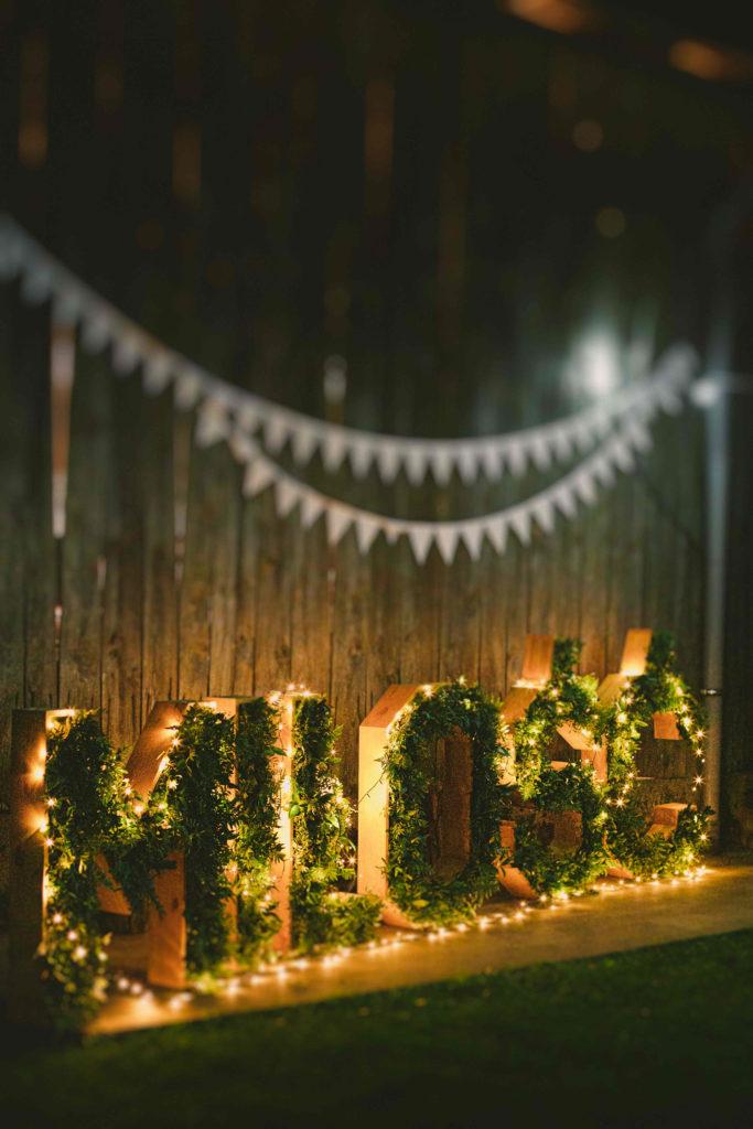 napis miłość z zieleni dekorowany lampkami przy stodole
