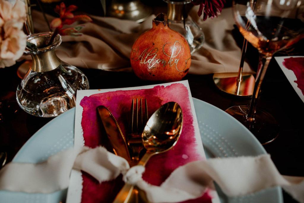 dekoracja talerza ozdobnym menu, złotymi sztućcami i jedwabną wstążką