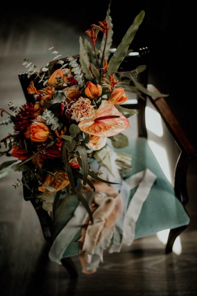 bukiet z tulipanów, anturium i eukaliptusów z długimi wstążkami na krześle