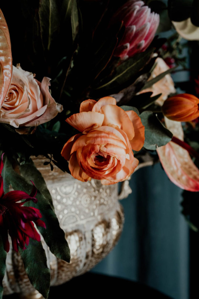kompozycja w złotej dużej wazie z pomarańczowymi i bordowymi kwiatami