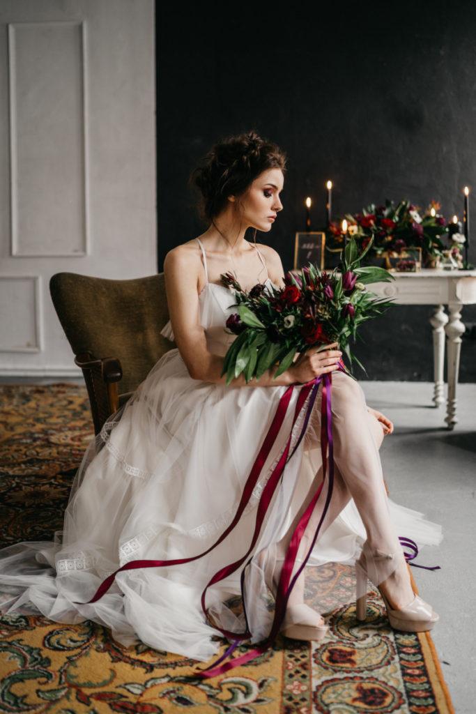 modelka z wiązanką ślubną w nietypowych kolorach z długimi wstążkami pozująca na krześle