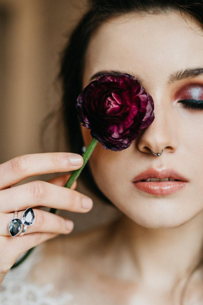 artystyczne zdjęcie z kwiatem prezentujące makijaż modelki
