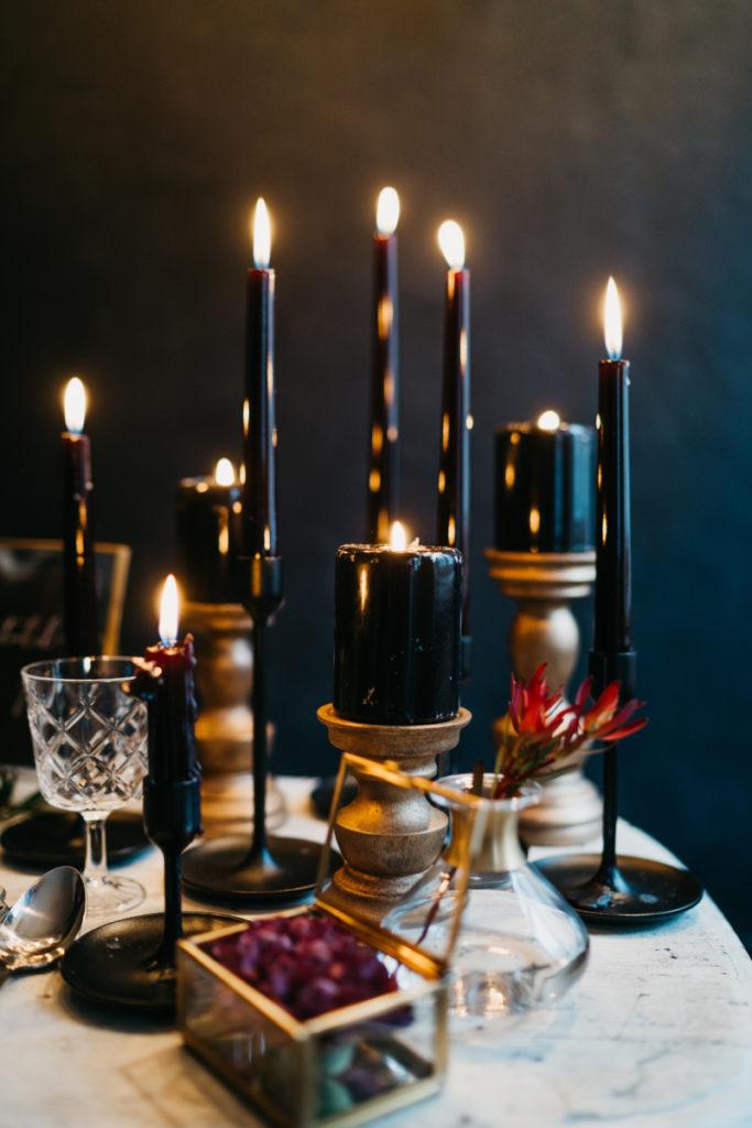 świece czarne na złotych świecznikach jako dekoracja stołu na sesje