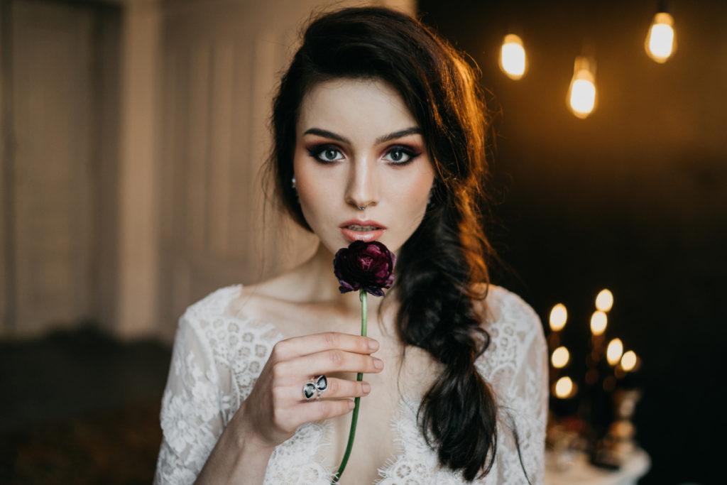 modelka z kwiatem promująca fryzurę oraz makijaż ślubny