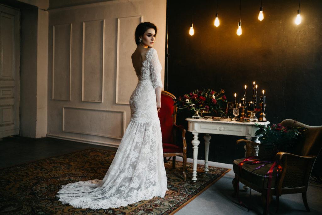 modelka w pięknej koronkowej sukni z trenem przy stole z dekoracjami w ciemnej kolorystyce