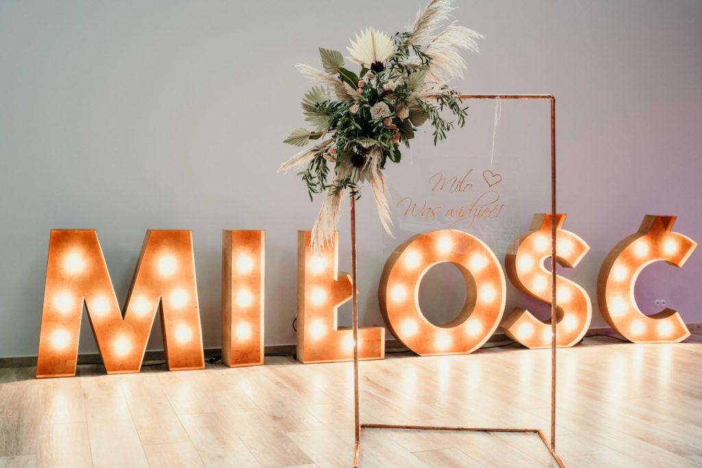 dekoracja stojaka miedzianego na tablicę powitalną oraz podświetlany napis miłość