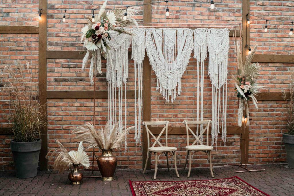 tło za parą młodą na plener w postaci miedzianego stojaka z makramą i dekoracją kwiatową z dodatkiem suszonych liści i traw pampasowych