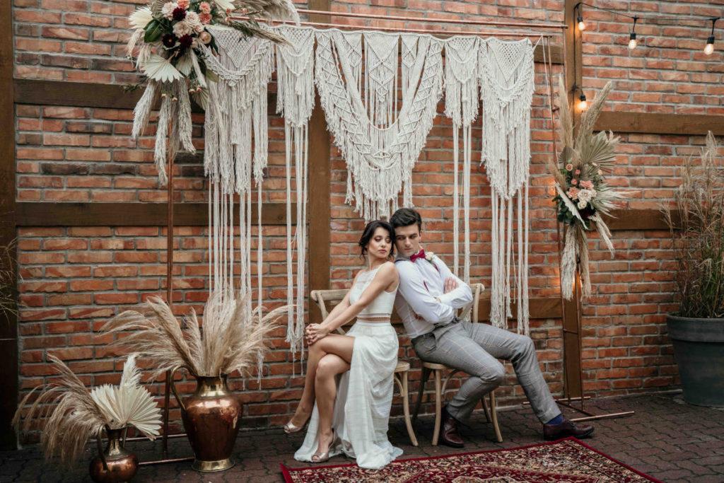 tło z makramy i dekoracji kwiatowych z trawami pampasowymi jako dekoracja ślubu w plenerze