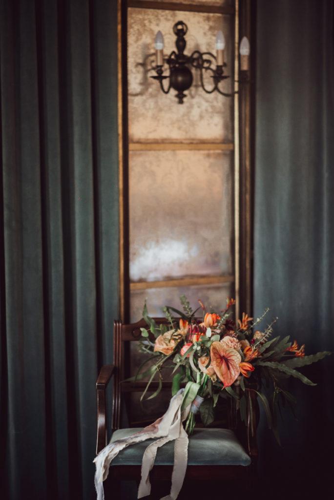 wiązanka ślubna ze zwisającymi wstążkami na krześle