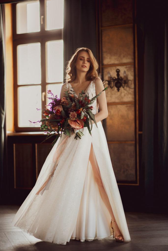 modelka w sukni ślubnej z bukietem kwiatów