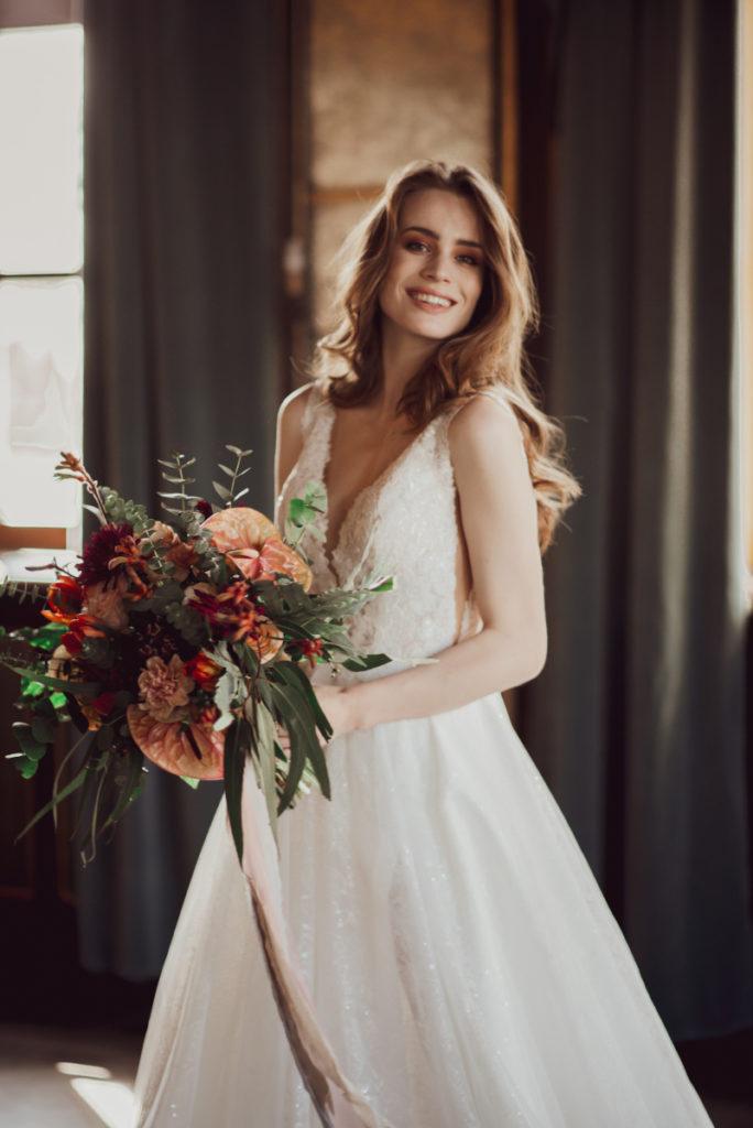 modelka w sukni ślubnej z wiązanką panny młodej