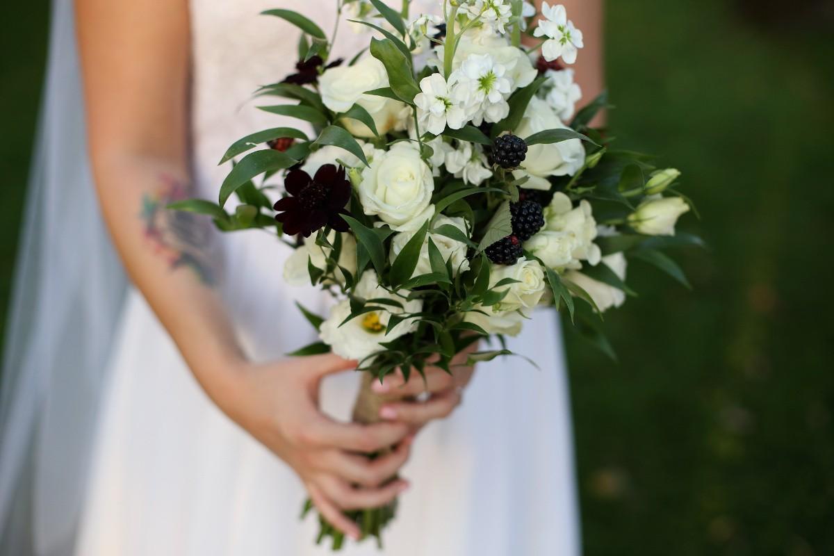 bukiet ślubny z białych kwiatów, zielonych listków i leśnych dodatków w postaci jeżyn