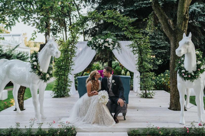 para młoda na tle łuku plenerowego w otoczeniu dekoracyjnych koni bukiet ślubny z białych storczyków